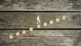 Man climbing a staircase of Bitcoins. In a concept of cyber currency investment, growth and success over a rustic wood background with copy space Stock Photography