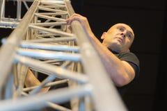 Man climbing on stairway metal tower. Man climbing on stairway of metal tower Stock Photography
