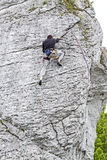 Man climbing steep and high rocky wall. Stock Photography