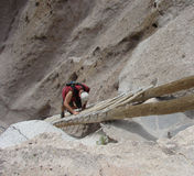 Man climbing steep ladder at cliff dwellings Stock Photography