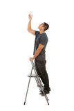 Man Climbing Stepladder To Replace Light Bulb Stock Photo