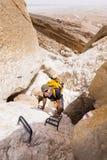 Man climbing stone desert gorge using iron steps stairs . Stock Image