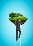 Man climbing to island in sky Royalty Free Stock Image
