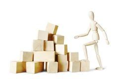 Man climbing to the stack of blocks Royalty Free Stock Image