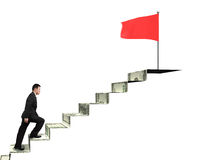 Man climbing to top for red flag on money stairs Royalty Free Stock Photos