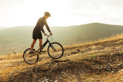 Man climbing on top of mountain. Man on trial bike riding up on the hill. Horizontal outdoors shot Stock Photos