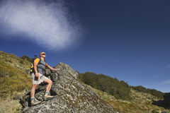 Man Climbing Up Boulder In Forest Valley Royalty Free Stock Images