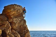 Man climbing up on mountain Stock Image
