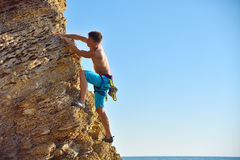 Man climbing up on mountain. Young man climbing up on yellow mountain on ocean background Stock Images