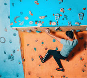 Man climbing up on practice wall Royalty Free Stock Photos