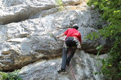 Man is climbing up a rock wall Royalty Free Stock Photo