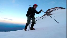 Man Climbing Up Snowy Mountain Ice Axe and Crampons stock footage