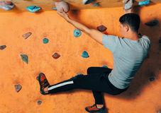 Man climbing up on wall indoors Stock Photos