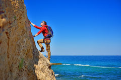 Man climbing up. Young man climbing up the rock on sea background stock image