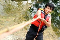 Man climbing using rope Stock Image
