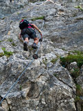 Man climbing on via ferrata Stock Image