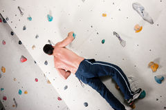 Man at the climbing wall Stock Images