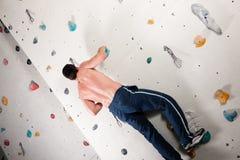 Man at the climbing wall Stock Images