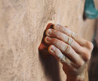 Man climbing on wall in gym, close-up of hand Royalty Free Stock Image