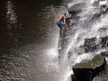 Man climbing waterfalls Stock Photos