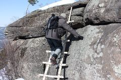 Man climbing a wooden staircase on the rock, Altai, RussiaRound, Bel Royalty Free Stock Photography