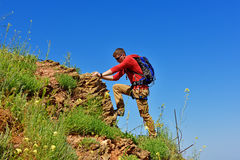 Man climbs on a cliff Stock Images