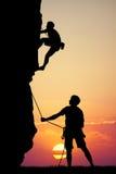 Man climbs mountain at sunset Stock Photography
