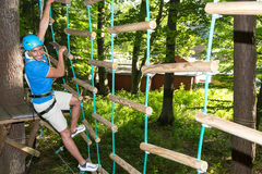 Man climbs over obstacles at high rope court Royalty Free Stock Image