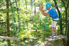 Man climbs over obstacles at high rope court Stock Images