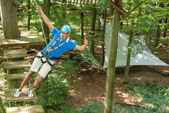 Man climbs over obstacles at high rope court Royalty Free Stock Photos