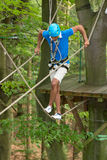 Man climbs over obstacles at high rope court Royalty Free Stock Images