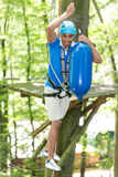 Man climbs over obstacles at high rope court Royalty Free Stock Photography