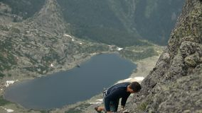 A man climbs a rock on a background of mountain lakes. stock footage