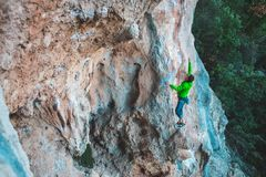 A man climbs the rock. Climbing in nature. Fitness outdoors. Active lifestyle. Extreme sports. The athlete trains on a natural relief Royalty Free Stock Photos