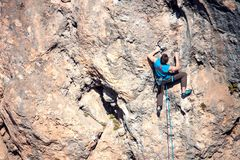 A man climbs the rock. Climbing in nature. Fitness outdoors. Active lifestyle. Extreme sports. The athlete trains on a natural relief Royalty Free Stock Images