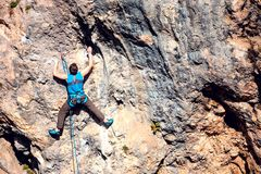 A man climbs the rock. Climbing in nature. Fitness outdoors. Active lifestyle. Extreme sports. The athlete trains on a natural relief Royalty Free Stock Photo