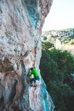 A man climbs the rock. Climbing in nature. Fitness outdoors. Active lifestyle. Extreme sports. The athlete trains on a natural relief Stock Photography