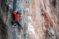 A man climbs the rock. Climbing in nature. Fitness outdoors. Active lifestyle. Extreme sports. The athlete trains on a natural relief Royalty Free Stock Photography