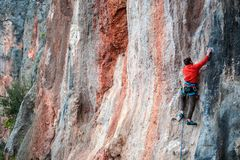 A man climbs the rock. Climbing in nature. Fitness outdoors. Active lifestyle. Extreme sports. The athlete trains on a natural relief Stock Image
