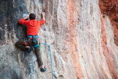 A man climbs the rock. Climbing in nature. Fitness outdoors. Active lifestyle. Extreme sports. The athlete trains on a natural relief Stock Photos