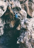 A man climbs the rock. Climbing in nature. Fitness outdoors. Active lifestyle. Extreme sports. The athlete trains on a natural relief. Rock climbing in Turkey Royalty Free Stock Photography