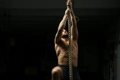 Man climbs ropa at gym Royalty Free Stock Image