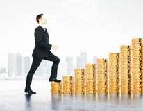 Man climbs the stairs of the coins at city background Royalty Free Stock Image