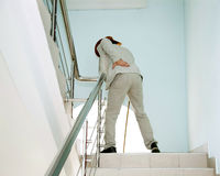 Man climbs the stairs with the pain in his back Royalty Free Stock Photography