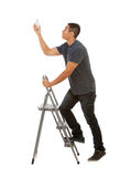 Man Climbs Stepladder To Replace Light Bulb Stock Photography