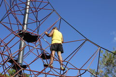 Man climbs to the top of a children's climbing frame. Stock Image