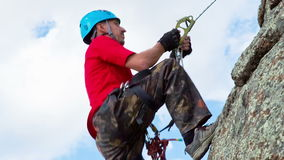 Man Climbs Up on top of the Rock Stock Image