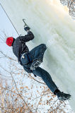Man climbs upward on ice climbing competition Stock Photo