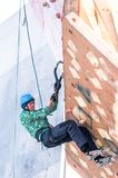 Man climbs upward on ice climbing competition Royalty Free Stock Photos