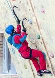 Man climbs upward on ice climbing competition Stock Photo